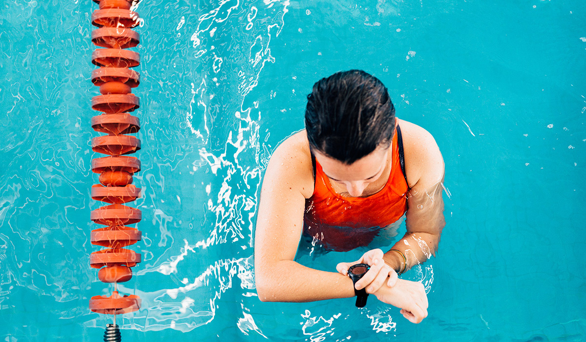 A person checking her watch in a swimming pool