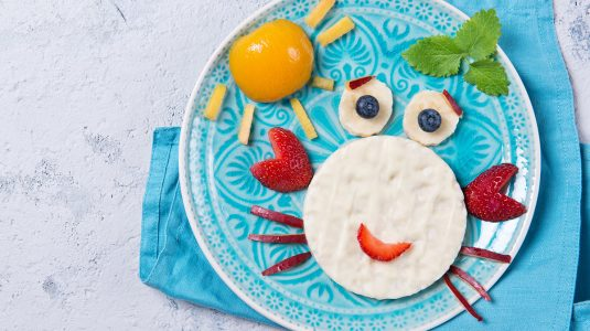 Rice waffles with yogurt in the shape of a crab with fresh fruits prepared for kids