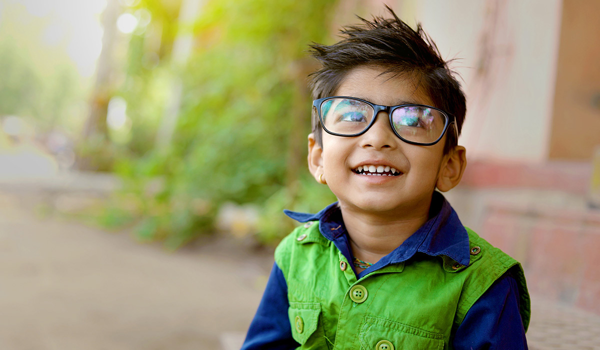 A smiling child with big glasses